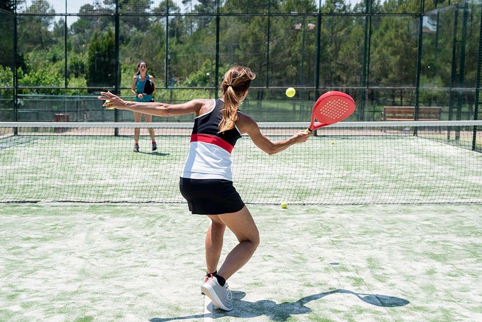 2 femmes jouent ua padel sur un court